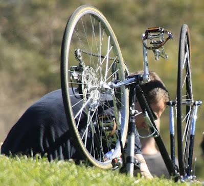 Man som mekar med upp- och nervänd cykel.