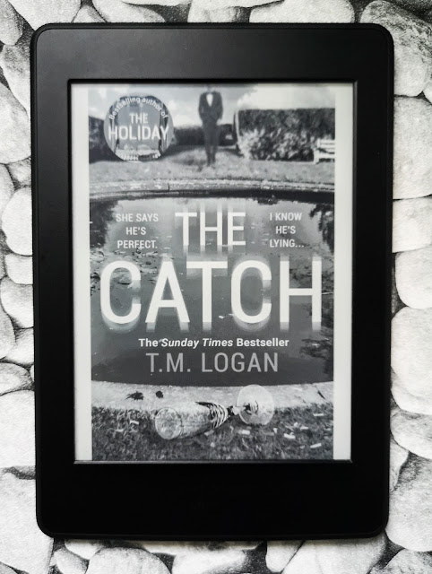 Image of a Amazon Kindle Paperwhite with the front cover of a digital ebook. The book is entitle The Catch by T. M Logan and has the tagline 'She say's he's perfect, I know he's lying' and the image is of a pool area, a man in a suit and a broken champagne flute in the foreground