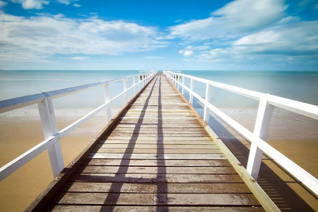 wooden pier with white rails leading to the sea
