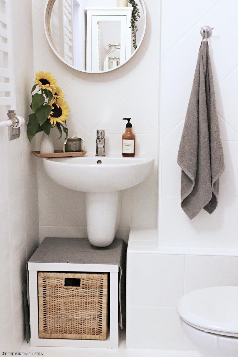 biała łazienka pomalowana farbą do płytek i okrągłe lustro w drewnianej ramie