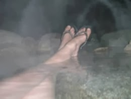 Feet soaking in a creek pool of natural hot springs.
