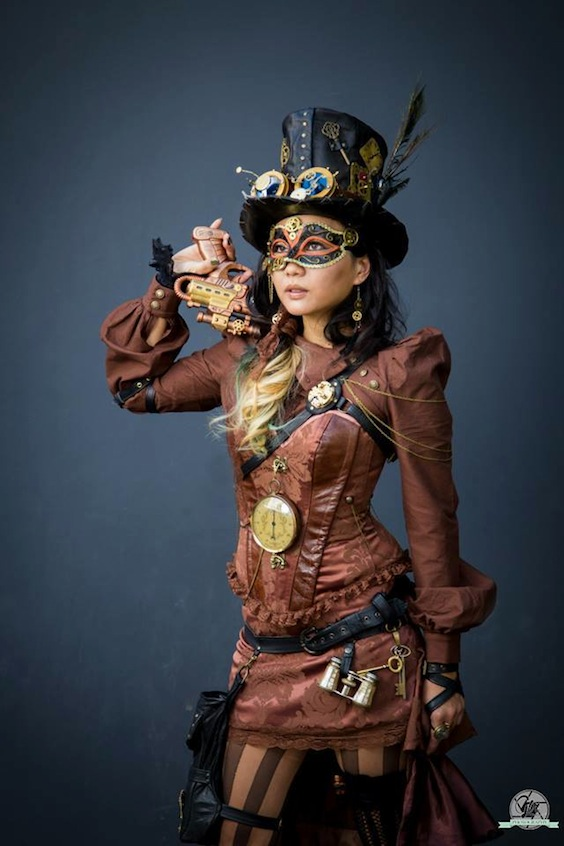 woman wearing brown steampunk clothing with black leather and gold accessories (top hat, mask, goggles, harness, thigh bag)