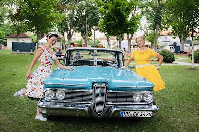 Corinna und Maria in kleidern von boutique new vintage an einem türkisen ford mustang lehnend bei rocknroll im kurpark Bad Sauerbrunn