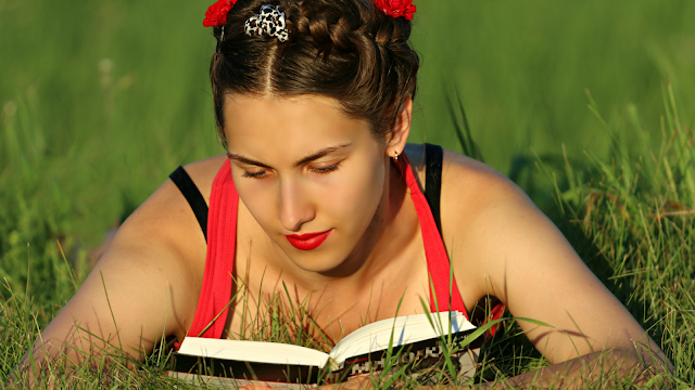 Young woman reading in grass