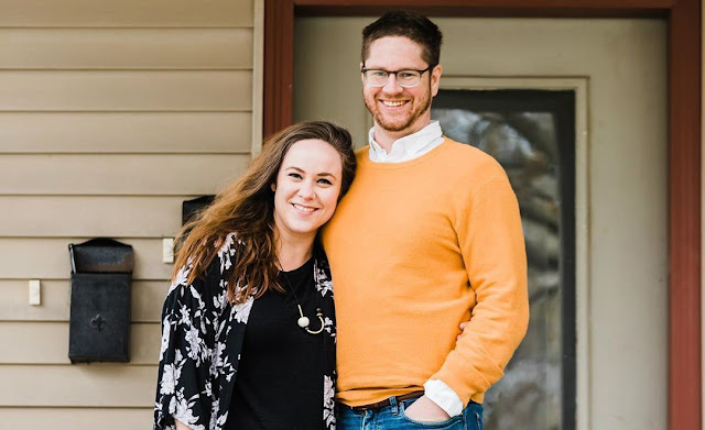 Smiling couple stands on a front porch