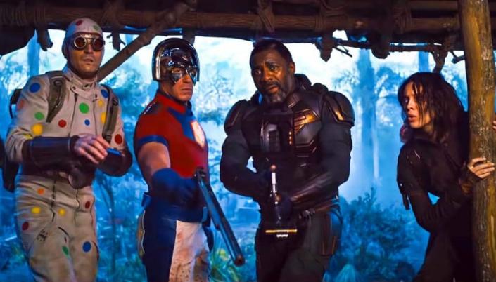 Imagem: os personagens Homem-Bolinha, em um traje branco com bolinhas coloridas, uma mochila e um par de óculos com lentes vermelhas, o Pacificador, um homem branco musculoso com uma camisa vermelha e um símbolo amarelo com uma pomba branca no peito e um elmo prateado e arrendondado, luvas azuis segurando uma enorme pistola, depois o Sanguinário, um homem negro com um traje tecnológico preto com detalhes azuis, e ao lado a Caça-Ratos, uma mulher branca com cabelos pretos curtos chegando aos seus ombros e um traje verde-escuro com capuz. Todos eles olham da porta de um tipo de cabana ou acampamento em uma floresta.