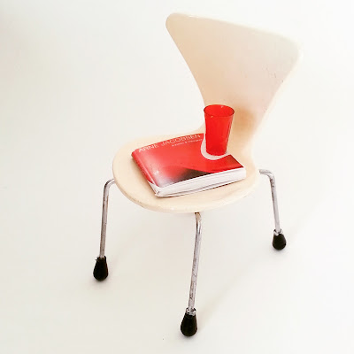 Modern dolls' house miniature white Arne Jacobsen series 7 chair, with a red book on Arne Jacobsen and glass on the seat.
