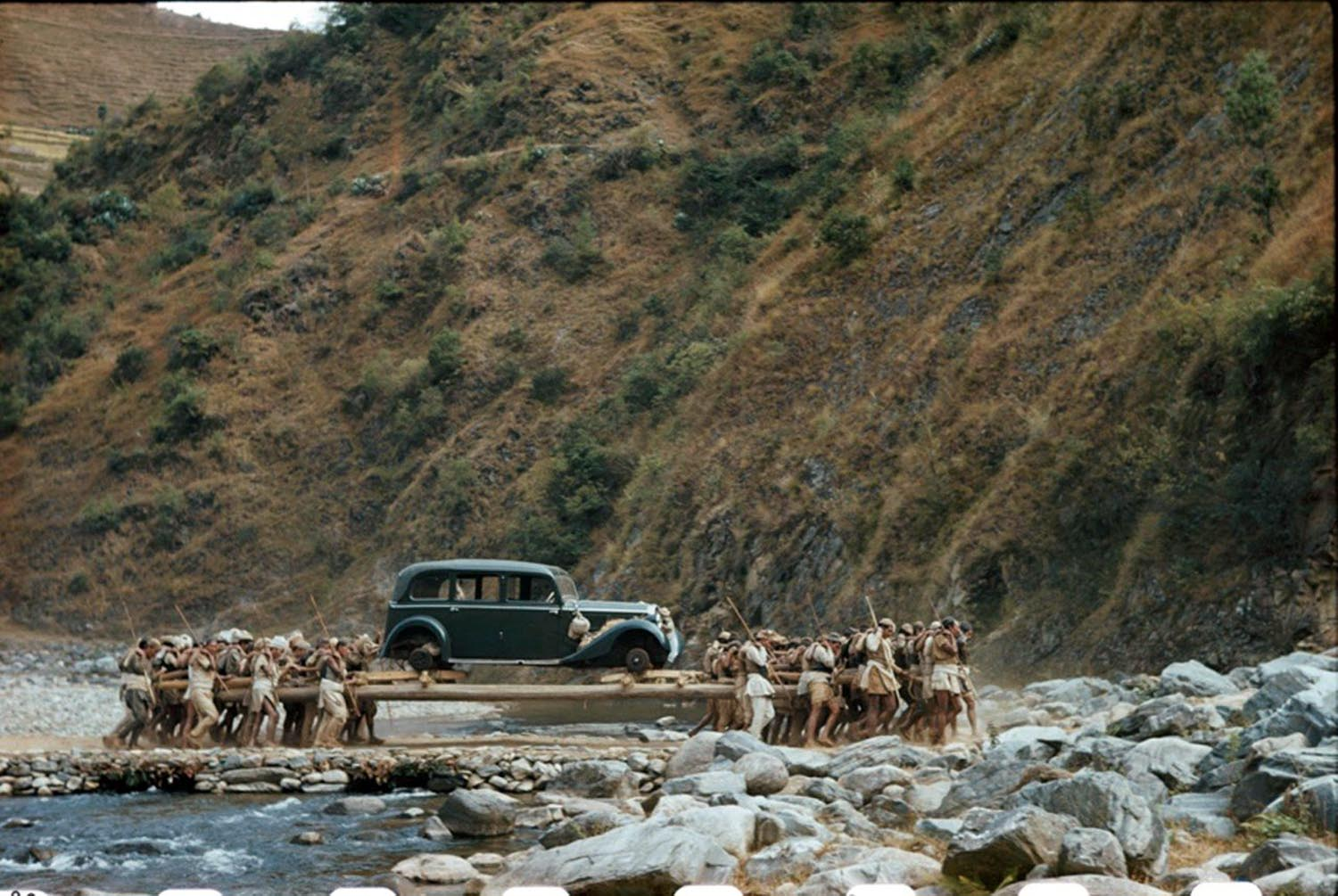 A team of sixty porters carry an old German-made Mercedes en-route to India, 1948