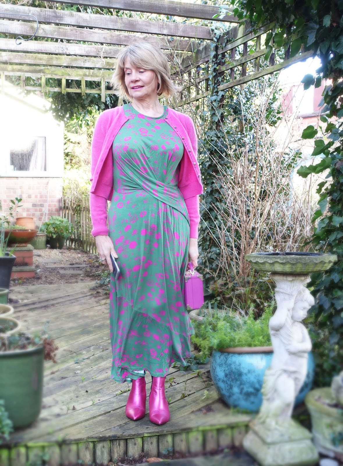 Gail Hanlon from over 50s style blog Is This Mutton? in midi length green and pink patterned dress, pink cardigan and pink metallic boots