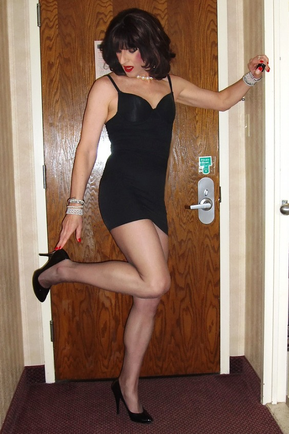Feminine girl wearing a black mini dress, black tights and black pumps high heels