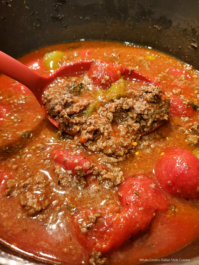 this is a pot of Venison Bolognese Sauce that has whole tomatoes, bell peppers and venison ground hamburger in tomato sauce simmering