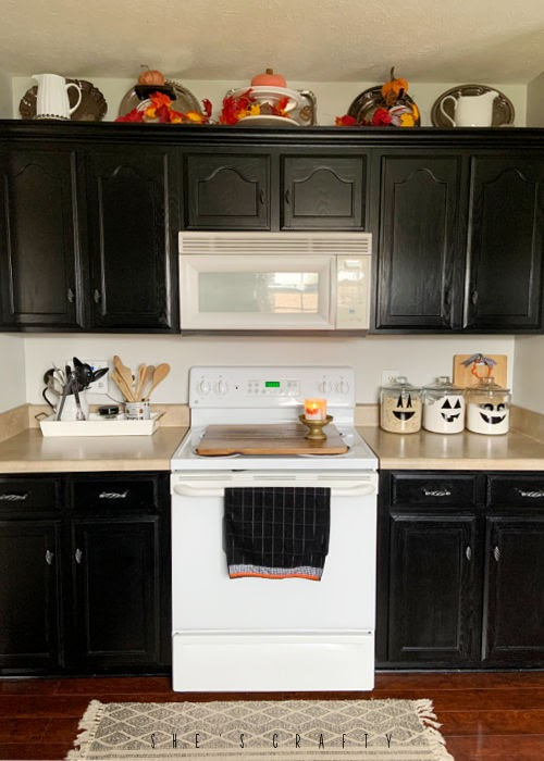 Halloween Home decor in the kitchen - put leaves, lights and pumpkins above cabinets