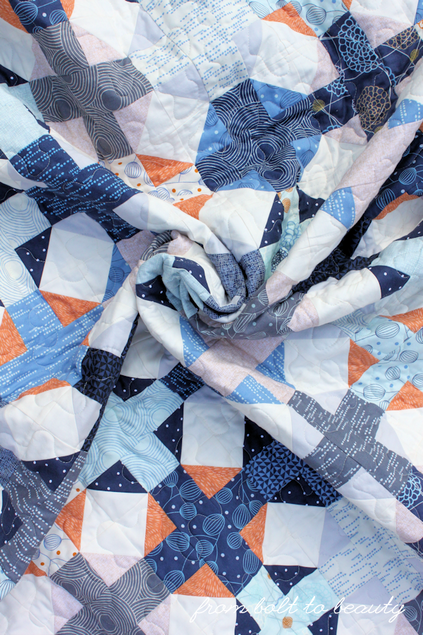 A quilt swirl in blues, grays, oranges, and whites.