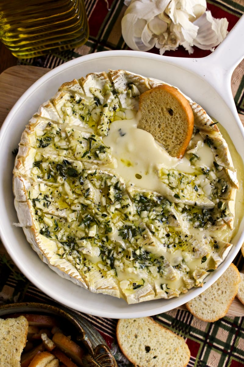 This Garlic and Herb Baked Brie topped with fresh herbs and loads of garlic is the ultimate appetizer for garlic lovers! It is elegant enough for holiday gatherings and easy enough for casual get-togethers. #brie #appetizerrecipes