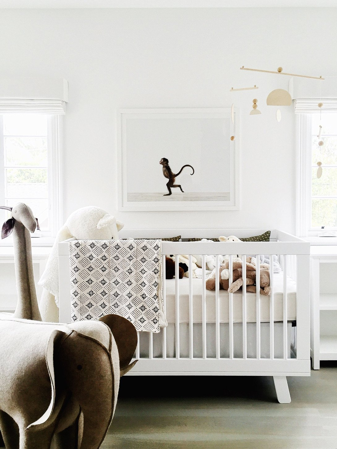 White nursery with modern farmhouse California organic chic design by Erin Fetherston. A modern white crib mingles with a charming and whimsical large framed photographic print of a monkey. #nursery #allwhite #kidsrooms
