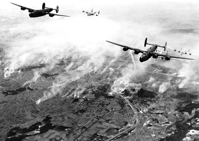 A formation of B-24s of Maj. General Nathan F. Twining's U.S. Army 15th Air Force thunders over the railway yards of Salzburg, Austria, on December 27, 1944. The smoke created by their bombs mingles with that from the enemy's many smudge pots.