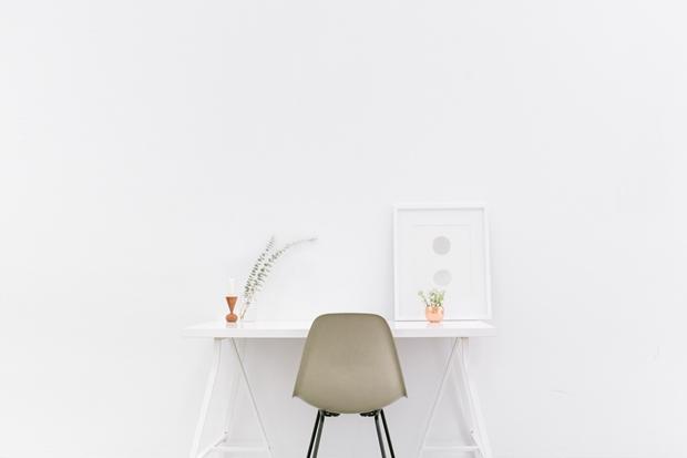 Decoração clean; mesa branca com uma cadeira em frente e um poster decorativo apoiado em cima