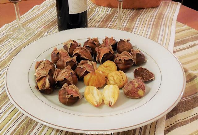 na talerzu pieczone kasztany obok butelka wina oraz dwa szklane kielszki