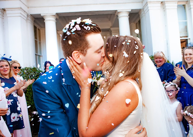 Bride and groom kiss with confetti