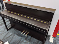 Kawai CA99 rosewood piano with closed key cover