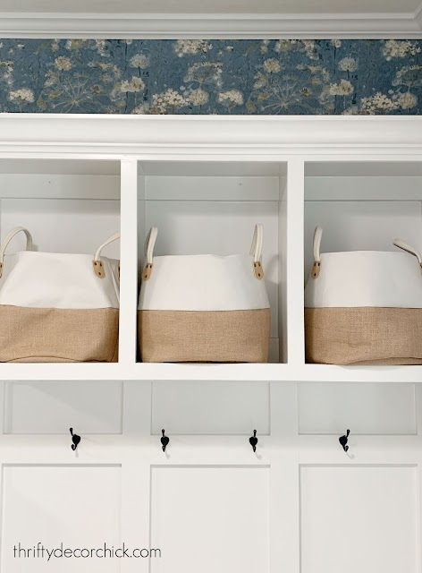 White mud room cubbies with blue floral wallpaper