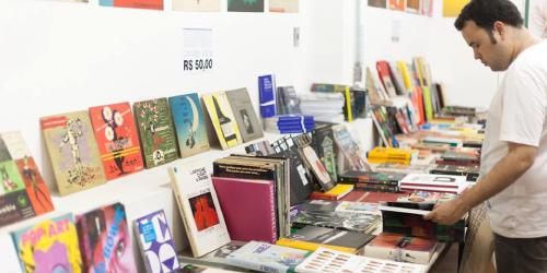 Imagem de capa do texto. Rennan em frente de uma bancada cheia de livros.