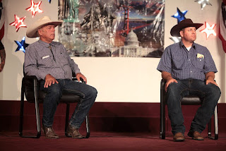 Photograph of Cliven and Ammon Bundy seated on a stage