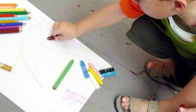 Barn som målar på ett papper på golvet