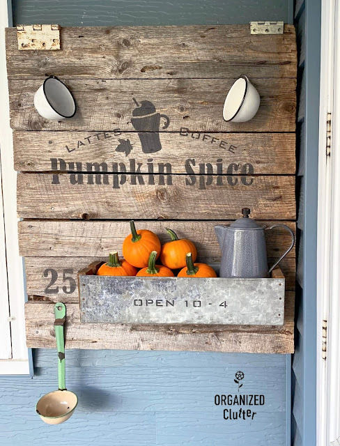 Photo of a barn door pumpkin spice latte sign with enamelware cups, galvanized drawer with pumpkins & a coffeepot, and a ladle/dipper.