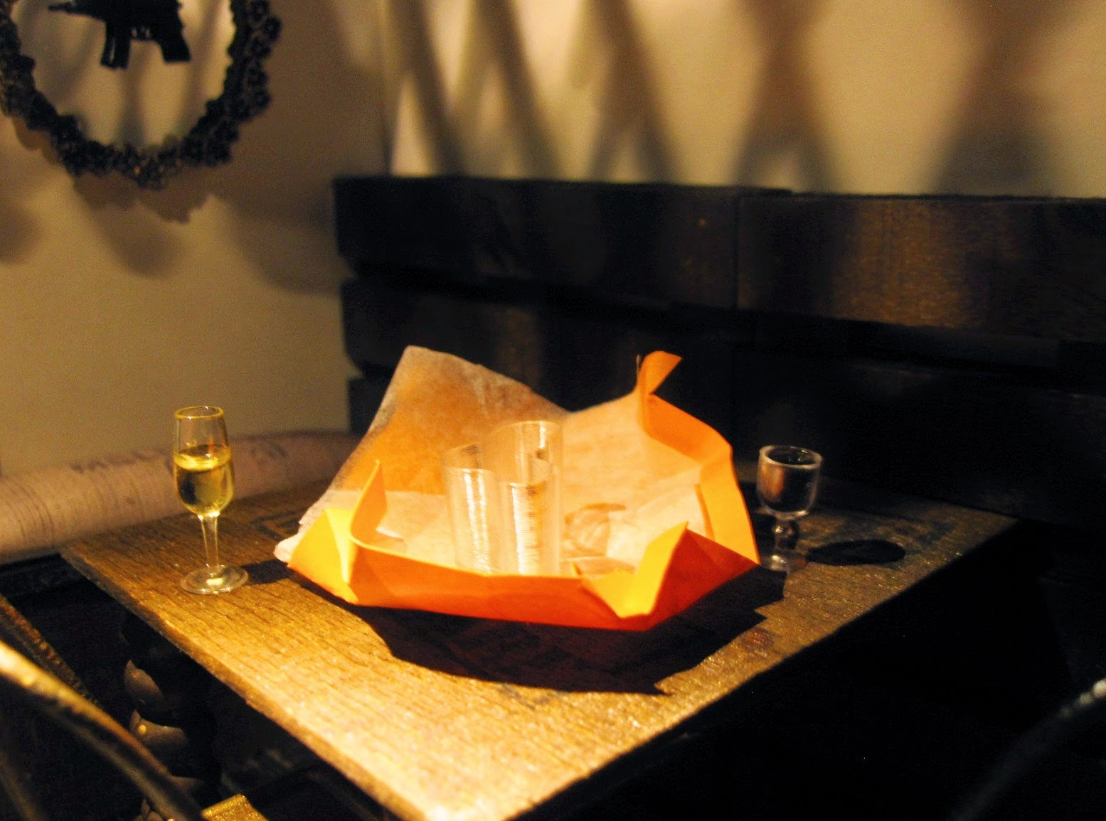 Interior of a modern dolls' house miniature cafe at night, with two glasses of wine and an unwrapped gift on the table.