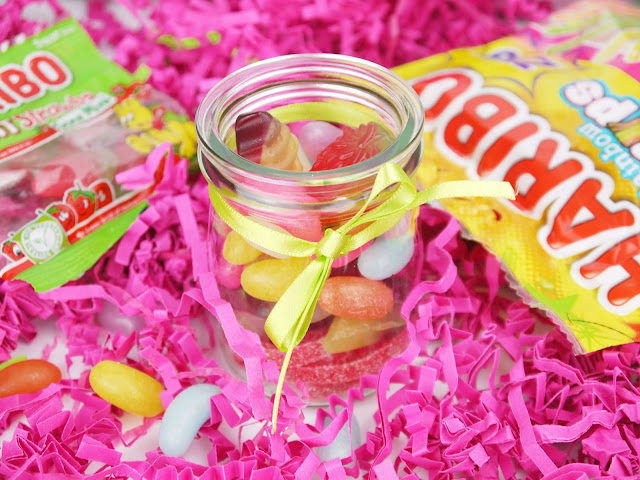 a mixture of Haribo vegetarian sweets in a small glass jar with a green ribbon around it, and pink shredded paper around it. To the left of the jar is a pack of strawberry sweets, rainbow strips on the right, and jelly beans in front.