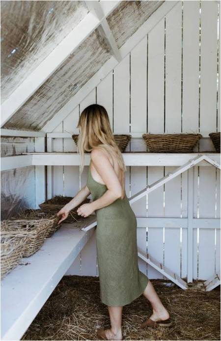 woman in a green dress standing in a barn