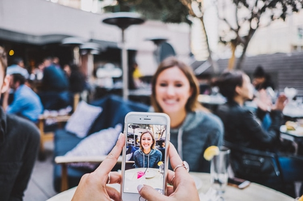 Foto de uma mulher sendo fotografa com o celular
