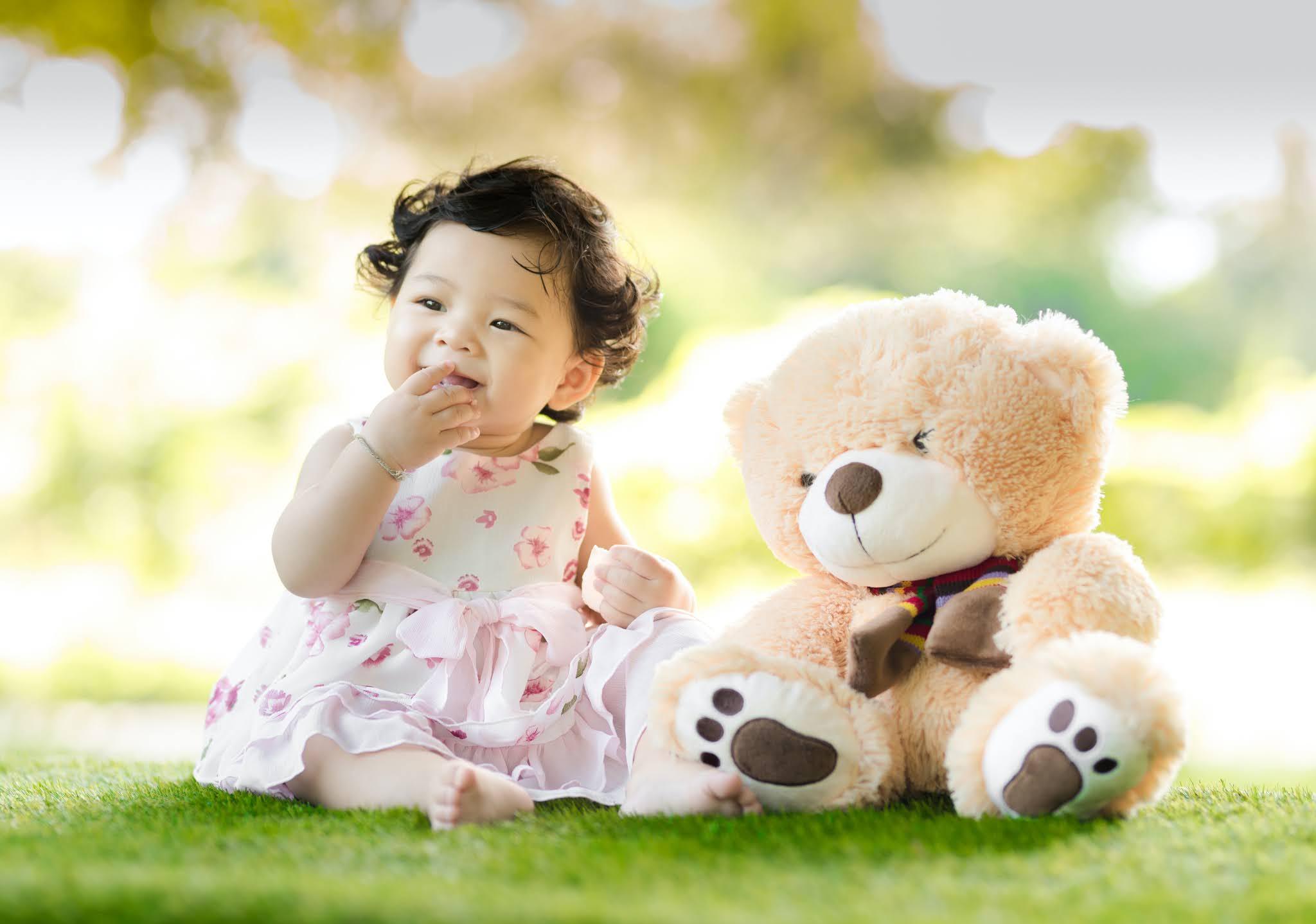 Bebê sentada na grama com o ursinho