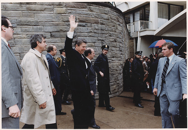 Reagan waves to the crowd; seconds later, John Hinkley, Jr shot Reagan in an assassination attempt.