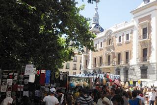 Numerosoas personas alrededor de los puestos de vendedores durante el mercado callejero de los domingos.