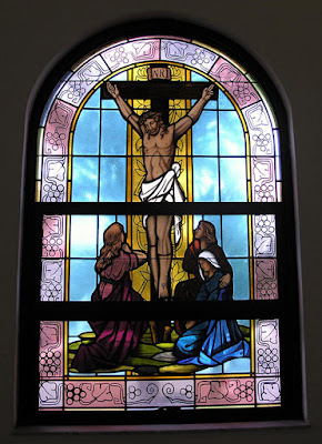 Stained glass window of Jesus on cross.