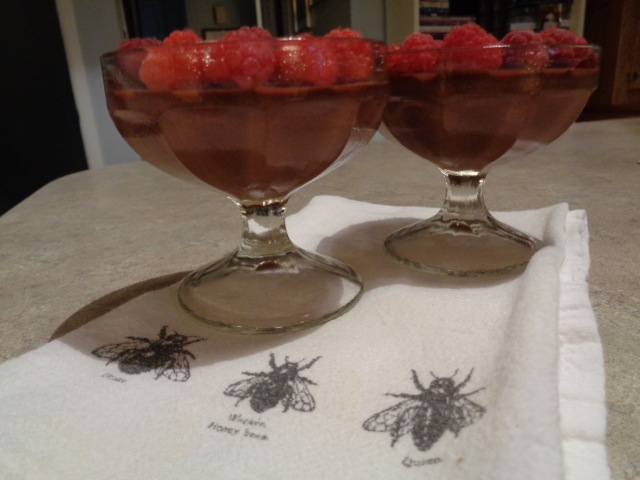Goblets of raspberries and ganache on a table
