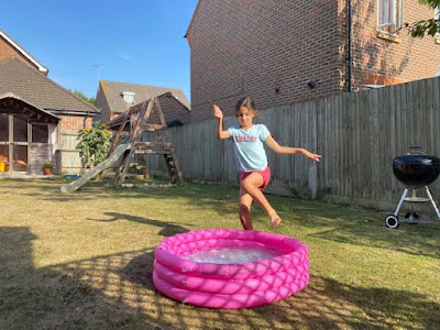 Child jumping into a paddling pool in the garden