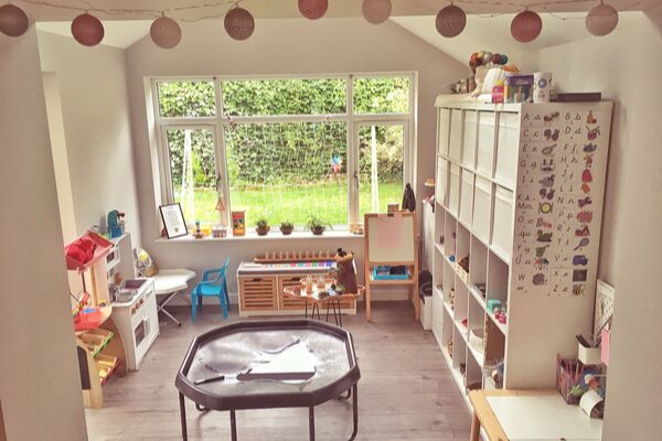 child-led playroom layout with tuff tray and open shelving