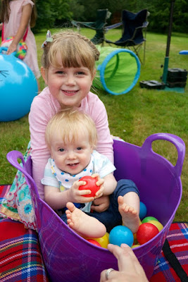 Sophie holding Thomas who is sitting in a trug
