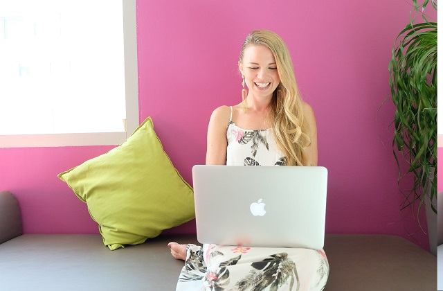happy pretty girl on laptop on couch with pink wall background