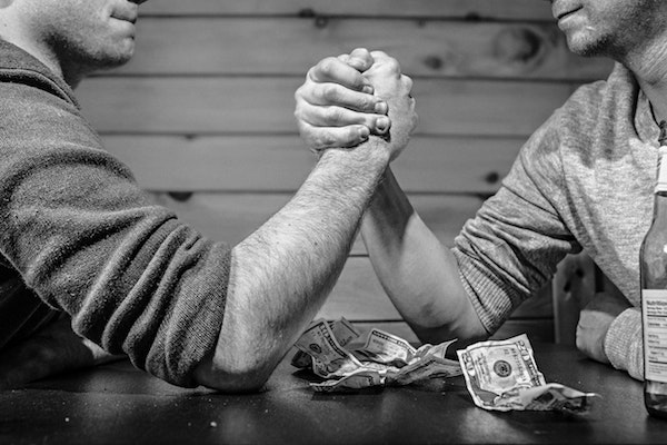 2 men arm wrestling over a pile of money