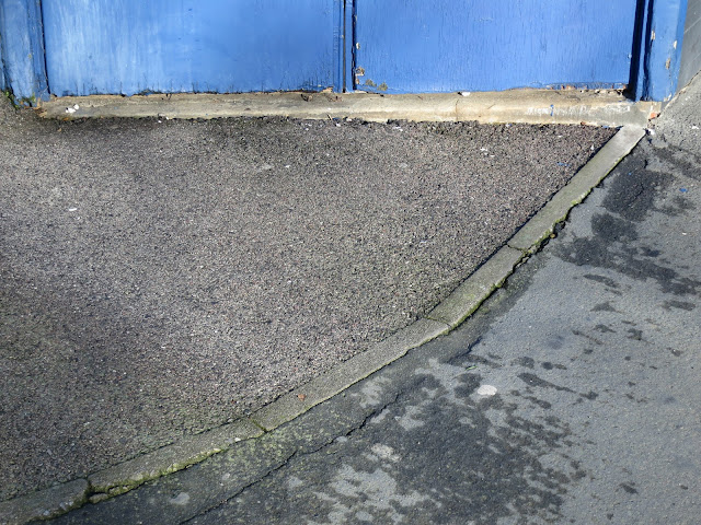 Curve in pavement in front of blue painted doors.