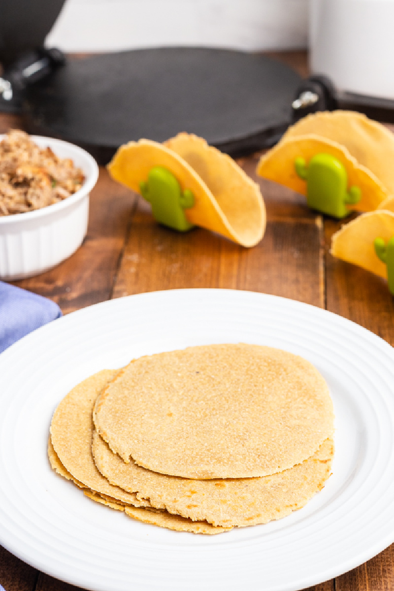 Photo of several keto flour tortillas on a white plate with a tortilla press in the background.