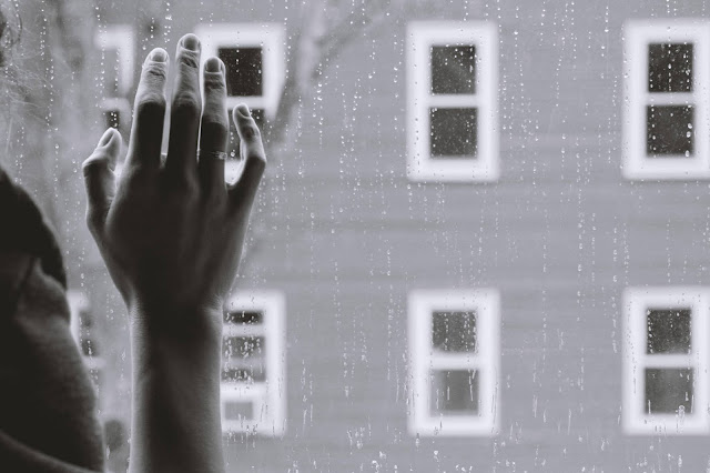 hand on window with raindrops sad:Photo by Kristina Tripkovic on Unsplash