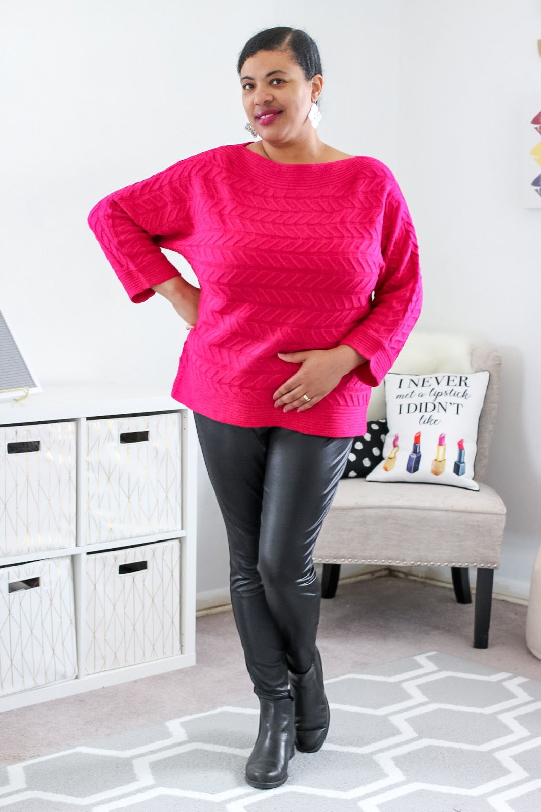 a woman posing wearing a pink sweater and black leggings