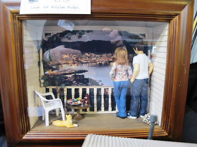 One-twelfth scale miniature scene of a woman and a man on a porch looking over a harbour view at night.