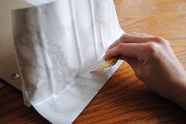 Een deel van het plakplastic zit vastgeplakt en wordt aangedrukt met een plastic pasje.