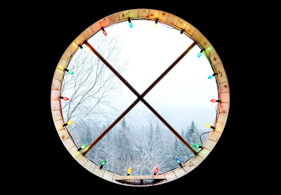 round window with X-panes, circled in christmas lights